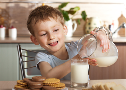 Healthy child pours milk from jug